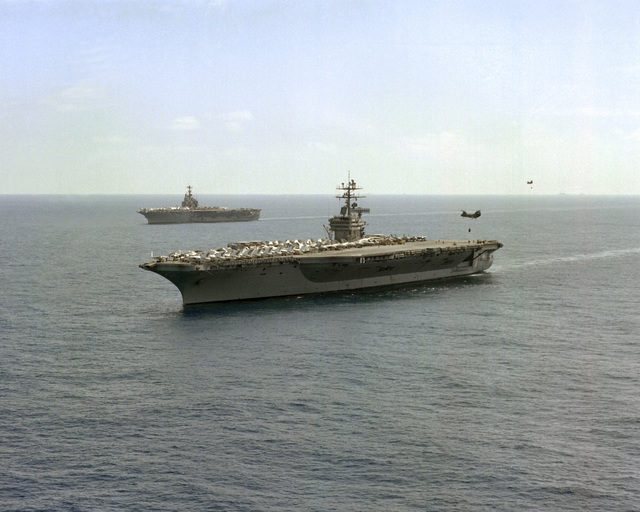 A port bow view of the nuclear-powered aircraft carrier USS DWIGHT D. EISENHOWER (CVN-69), foreground, with a CH-46 Sea Knight helicopter at the stern, as she is relieved from deployment by the aircraft carrier USS INDEPENDENCE (CV-62)