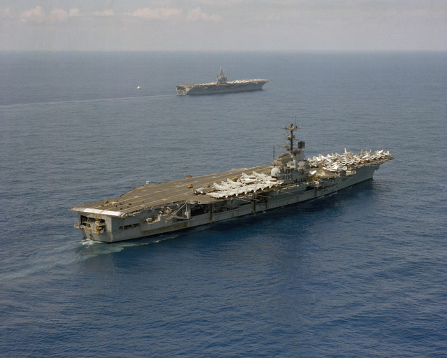 An elevated starboard quarter view of the aircraft carrier USS INDEPENDENCE (CV-62), foreground, sailing by the nuclear-powered aircraft carrier USS DWIGHT D. EISENHOWER (CVN-69). The EISENHOWER is on deployment and is being relieved by the INDEPENDENCE