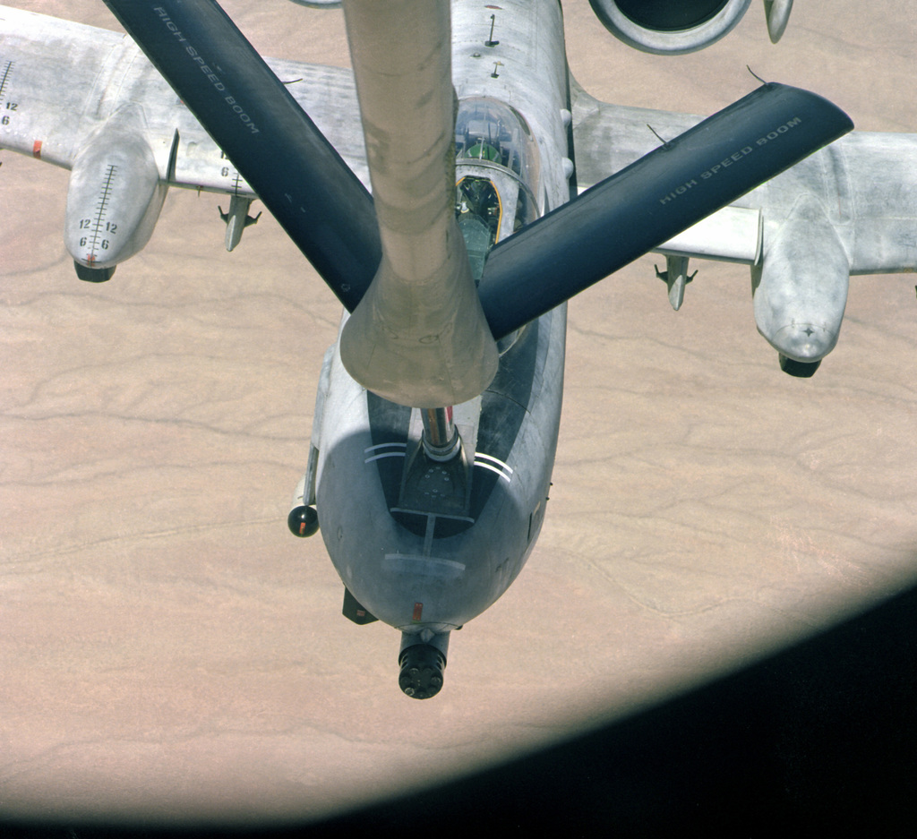 The nose of an in-flight A-10 as the aircraft is refueled through the boom of a KC-135 Stratotanker aircraft during testing. The photograph was taken from the KC-135's boom section