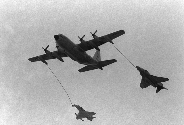 A KC-130 Hercules aircraft refuels an F-4 Phantom II aircraft, right, and an A-6 Intruder aircraft in flight