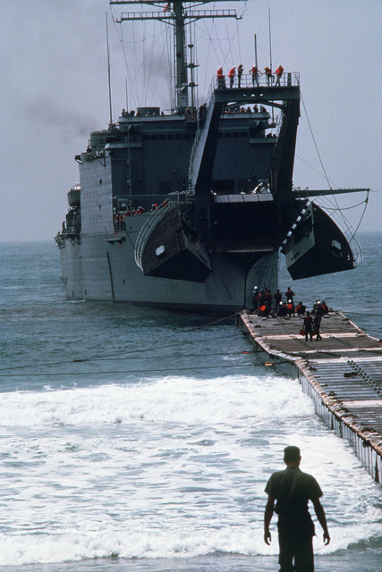 Crewmen stand at the end of a causeway as the tank landing ship USS SAN BERNARDINO (LST 1189), with bow open, prepares to lower its ramp