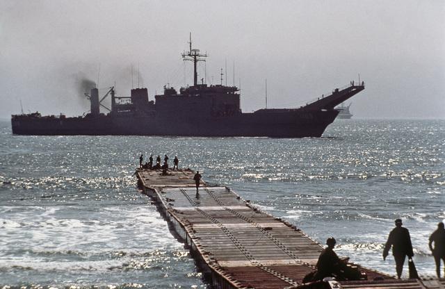Sailors wait on a causeway as the tank landing ship USS SAN BERNARDINO (LST 1189) approaches