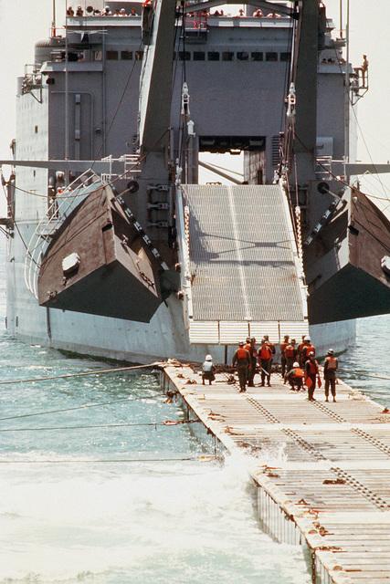 The tank landing ship USS SAN BERNARDINO (LST 1189) lowers its ramp to a causeway as crewmen stand by