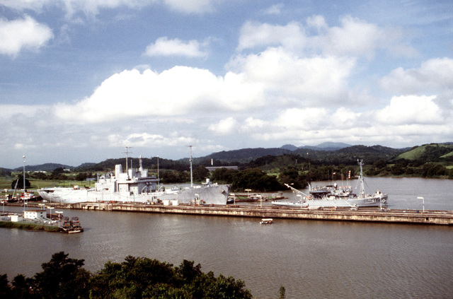 A starboard side view of the missile range instrumentation ship USNS OBSERVATION ISLAND (T-AGM 23) as the salvage ship USNS OPPORTUNE (T-ARS 41) tows it through the Miraflores Locks while en route to the Pedro Miguel Locks
