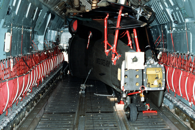 A UH-60A Black Hawk helicopter is loaded into a C-141 Starlifter aircraft. Members of the 101st Airborne Division are loading two UH-60A helicopters aboard a C-141 during testing of a new transportability kit