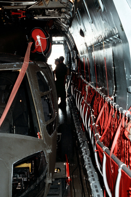 An interior view of a C-141 Starlifter aircraft showing side-to-side clearance with a UH-60A Black Hawk helicopter aboard. Members of the 101st Airborne Division are loading two UH-60As into the C-141 during testing of a new transportability kit