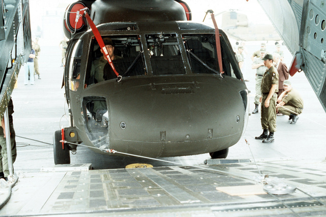 Members of the 101st Airborne Division load a UH-60A Black Hawk helicopter into a C-141 Starlifter aircraft. Two UH-60A helicopters are being loaded aboard the C-141 during testing of a new transportability kit
