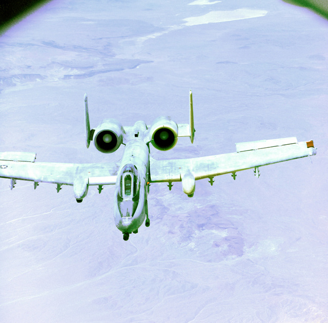An overhead front view of an A-10 Thunderbolt II aircraft in flight during an engine icing test. The photograph was taken from the boom section of a KC-135 Stratotanker aircraft