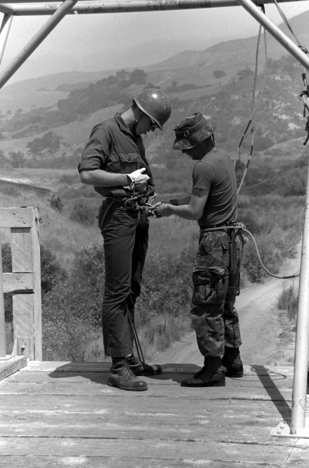 A midshipmen is instructed by a Marine instructor on how to put on a rope during rope rappelling class at the Infantry Training School. The midshipman is on his collge spring break and is touring Camp Pendleton with other many other midshipmen