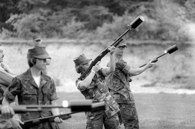 SGT. Jeanne E. Jacko fires a Remington 870 pump action shotgun equipped with a riot control canister. Lance CPL. Julie Ann Williams is standing to the right waiting for her turn to fire the shotgun. Shotgun familiarization is part of the training for Marine security guard students at the Marine Corps Development and Education Command