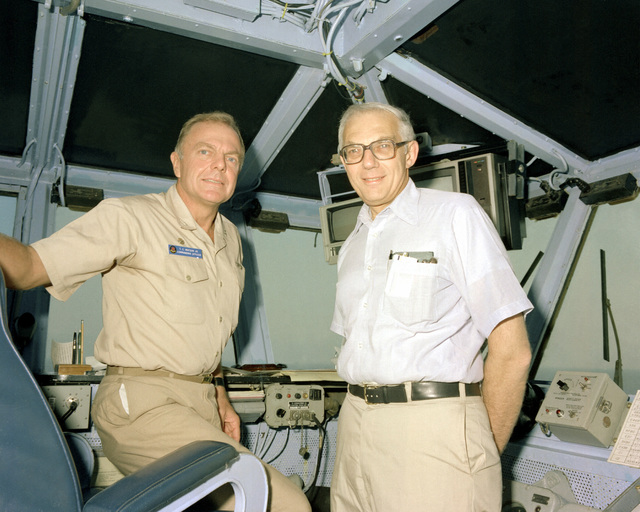 Undersecretary of the Navy David Mann, right, and CAPT Thomas C. Watson Jr., commanding officer, on the bridge of the USS INDEPENDENCE (CV-62) during Mann's visit aboard the aircraft carrier