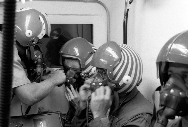 An instructor adjusts the oxygen mask for one of the Marine students during their low compression chamber test