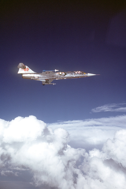 A low angle right side view of an F-104 Starfighter aircraft carrying two AIM-9J Sidewinder missiles in flight. The aircraft of the 69th Tactical Fighter Training Squadron, 68th Tactical Training Wing, 12th Air Force, is involved in Tactical Training Luke