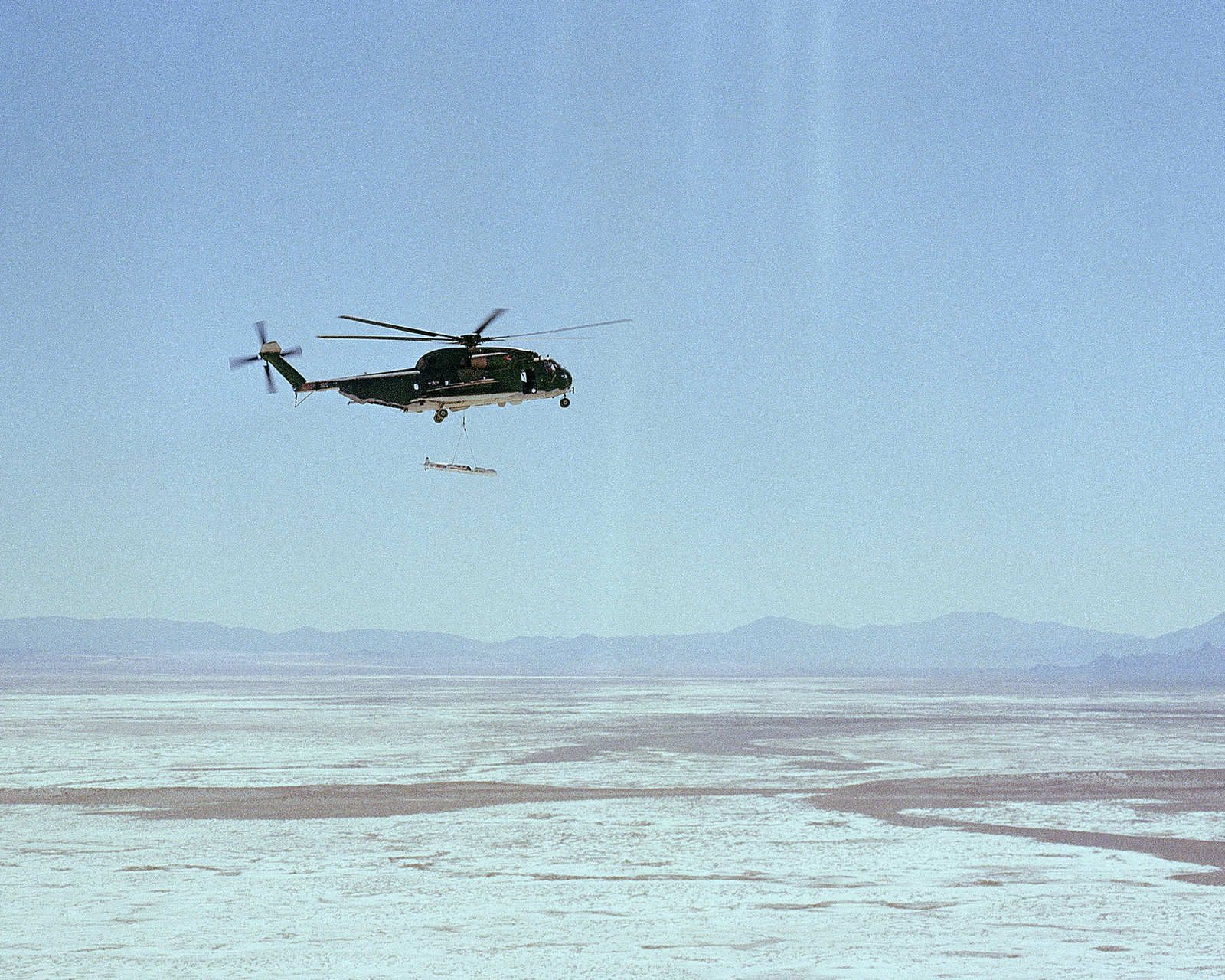 A right side view of a CH-53 Super Jolly helicopter airlifting an AGM-109 Tomahawk air-launched cruise missile during recovery operations after impact