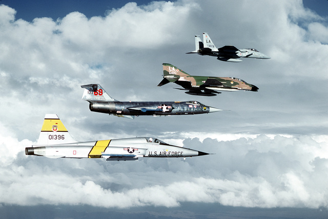 A right side view of an F-15 Eagle, F-4C Phantom II, F-104 Starfighter, and F-5 Tiger II aircraft, top to bottom, on a Tactical Training Luke training mission. The aircraft are, respectively, from the 550th, 310th, 69th, and 425th Tactical Fighter Training Squadron, all under the 12th Air Force