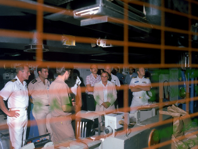 CAPT Thomas C. Watson Jr., left, commanding officer, and crewmen give distinguished guests a tour of the combat information center (CIC) aboard the aircraft carrier USS INDEPENDENCE (CV-62)