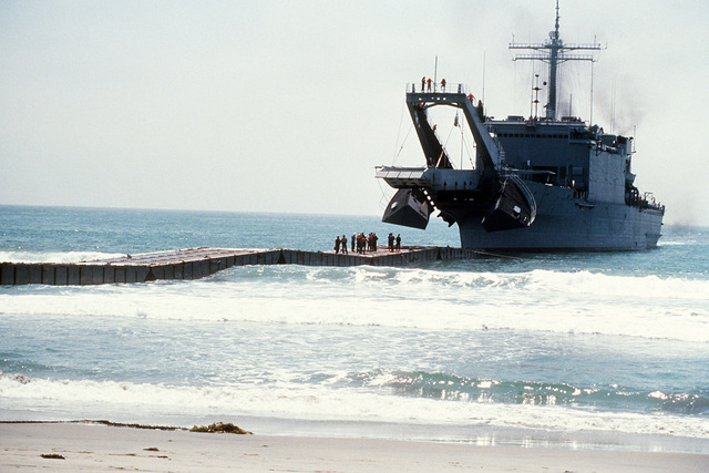 Crewmen stand at the end of a causeway as the tank landing ship USS SAN BERNARDINO (LST-1189), with bow open, prepares to lower its ramp