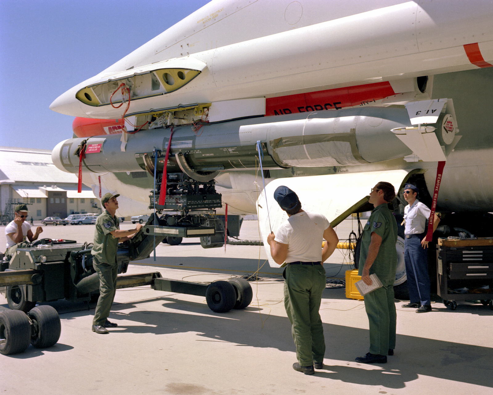 A ground crew loads an AGM-109 Tomahawk air-launched cruise missile on a B-52 Stratofortress aircraft