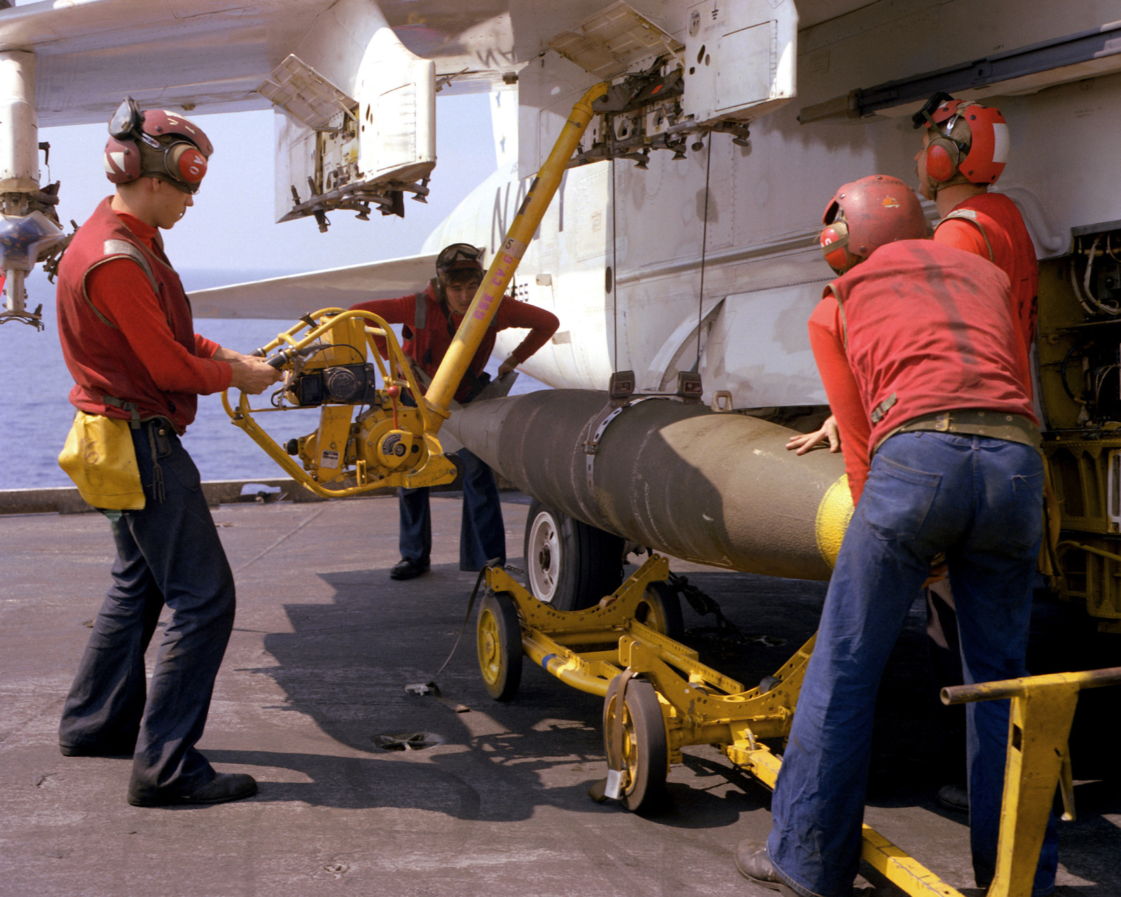 Four flight deck crewmen aboard the aircraft carrier USS INDEPENDENCE (CV-62) attach a missile to the wing of an A-7 Corsair II aircraft