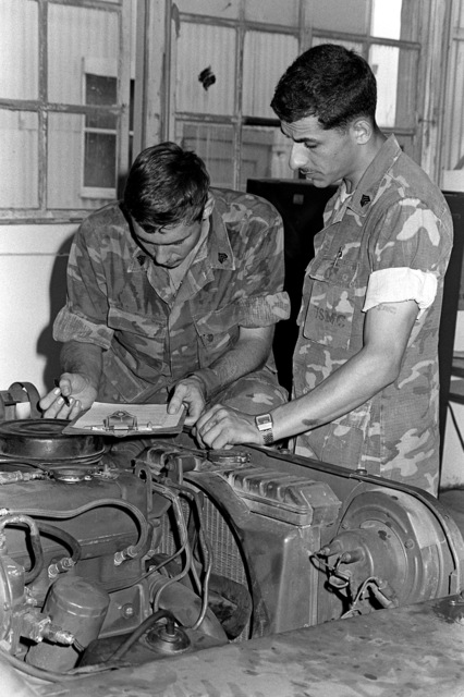 Marine SGT Elie Karam instructs SGT Richard Hill, left, on how to complete a preventive maintenance check off list for the motor transport section. Both men are members of the Marine Wing Support Group 17, Detachment C