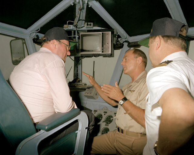 CAPT Thomas C. Watson Jr., center, commanding officer, explains the function of the bridge to Dr. Hiehle, a distinguished visitor aboard the aircraft carrier USS INDEPENDENCE (CV-62)