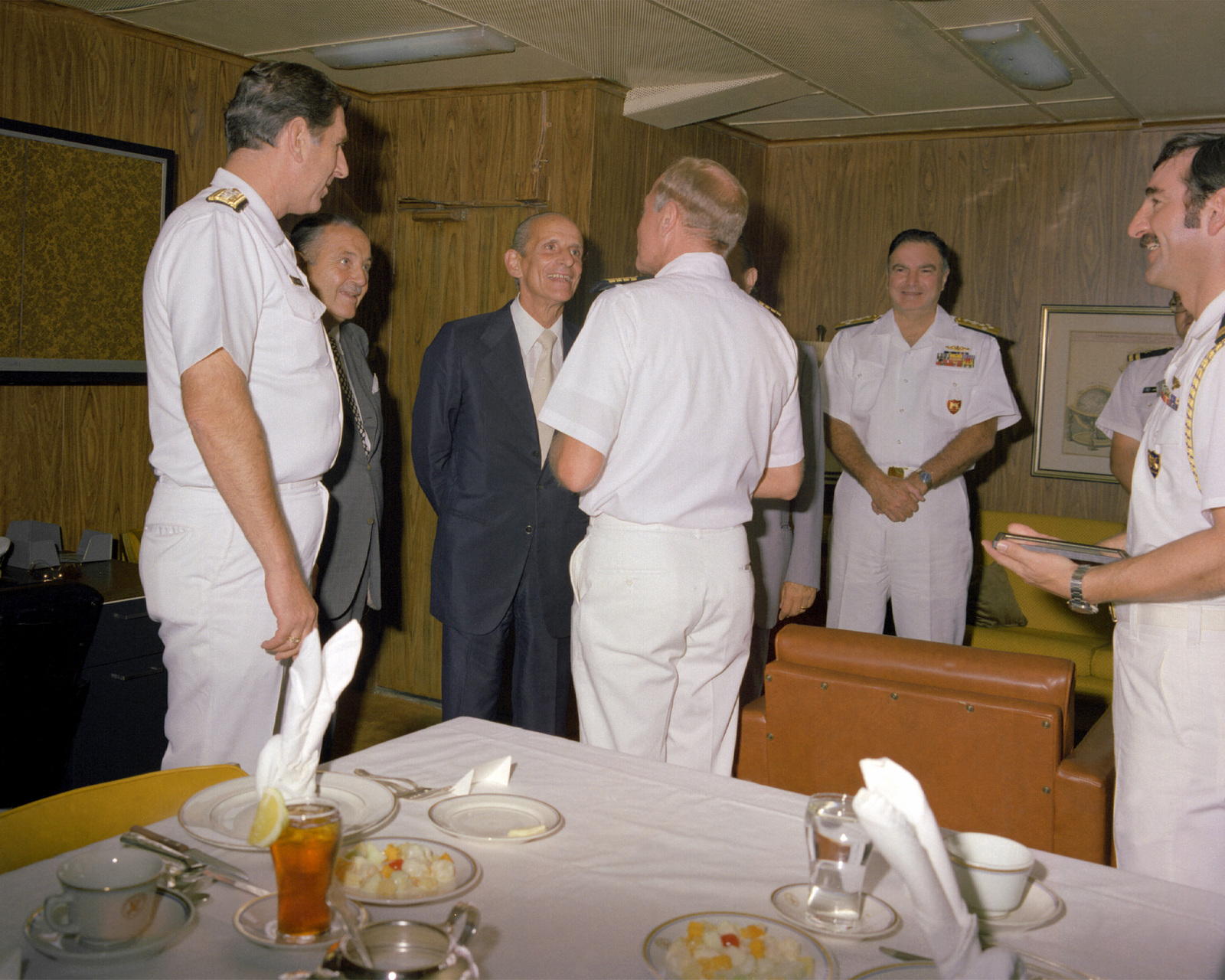 Aides watch as RDML James R. Sanderson, left, and CAPT Thomas C. Watson Jr., commanding officer, welcome the mayor of Naples for a visit aboard the aircraft carrier USS INDEPENDENCE (CV-62) and for a meal in the officers' mess
