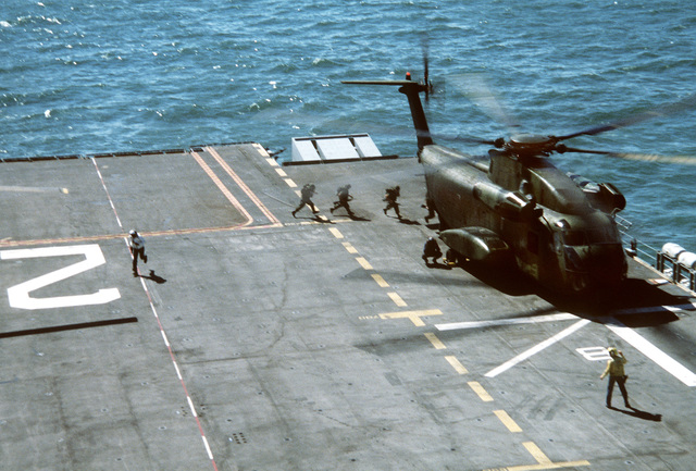 Marines cross the deck of the amphibious assault ship USS SAIPAN (LHA-2) to board a Marine CH-53 Sea Stallion helicopter