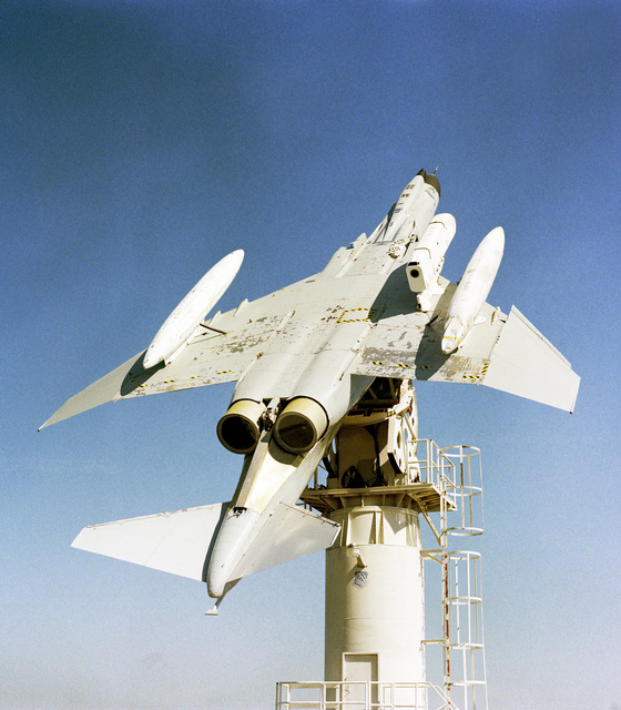 A view of an F-4E Phantom II aircraft mounted upside-down on a test tower at the Rome Air Development Center Newport site. Attached to the undercarriage of the F-4E is a special electronics pod holding a Joint Tactical Information Distribution System (JTIDS)