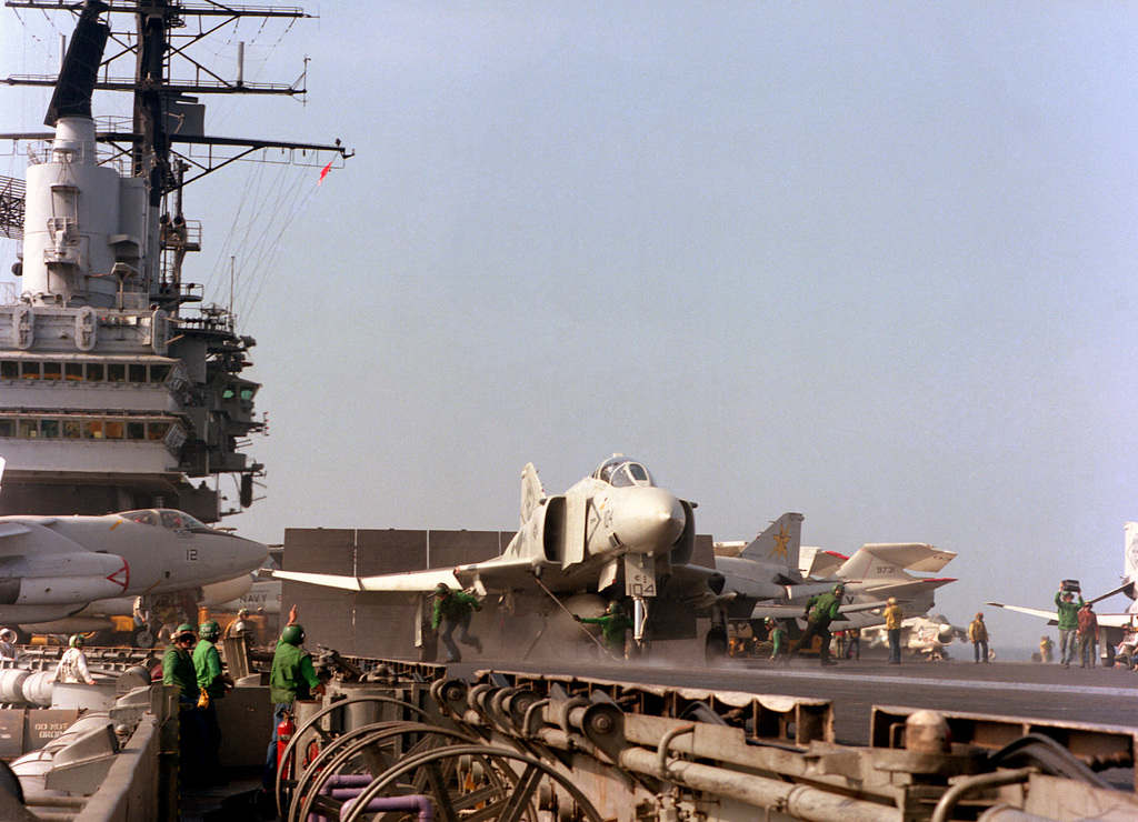 A front view of an F-4J Phantom II aircraft from Fighter Squadron 102 (VF-102) just prior to launch from the flight deck of the aircraft carrier USS INDEPENDENCE (CV-62). The aircraft is assigned to Carrier Air Wing 7 (CVW-7)