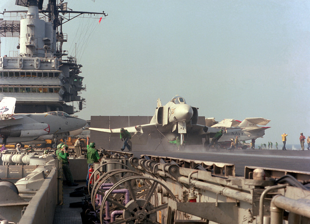 A right front view of an F-4J Phantom II aircraft from Fighter Squadron 33 (VF-33) being prepared for launching from the flight deck of the aircraft carrier USS INDEPENDENCE (CV-62). The aircraft is assigned to Carrier Air Wing 7 (CVW-7)