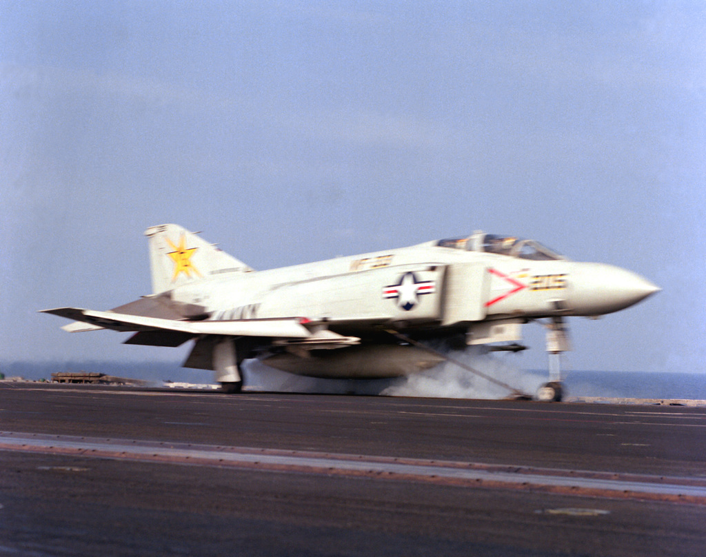 A right front view of an F-4J Phantom II aircraft from Fighter Squadron 33 (VF-33) just prior to launch from the flight deck of the aircraft carrier USS INDEPENDENCE (CV-62). The aircraft is assigned to Carrier Air Wing 7 (CVW-7)