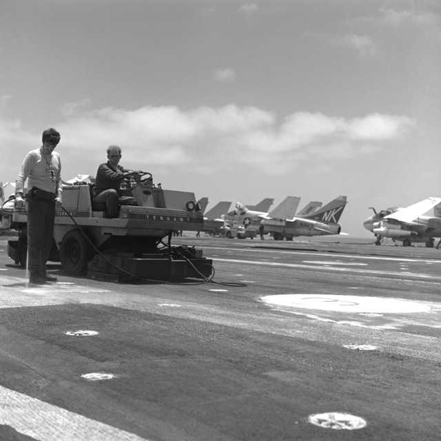 Crew members perform maintenance on the flight deck of the aircraft carrier USS CORAL SEA (CV-43). Parked in the background are A-7E Corsair II aircraft and an A-6E Intruder aircraft, right