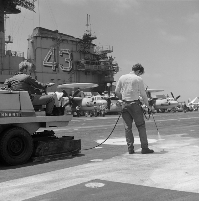 Crew members perform maintenance on the flight deck of the aircraft carrier USS CORAL SEA (CV 43). Parked in the background are E-2 Hawkeye aircraft