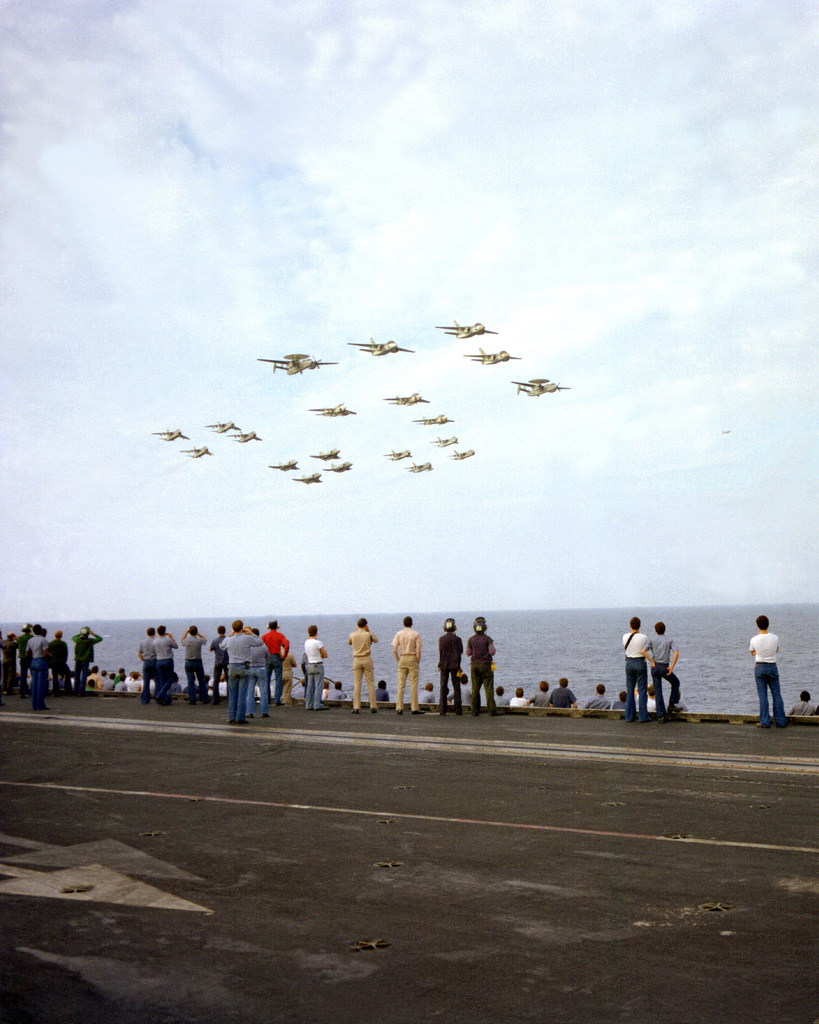 Crewmen watch from the flight deck of the USS INDEPENDENCE (CV-62) as aircraft from each squadron stationed aboard the aircraft carrier fly by in formation
