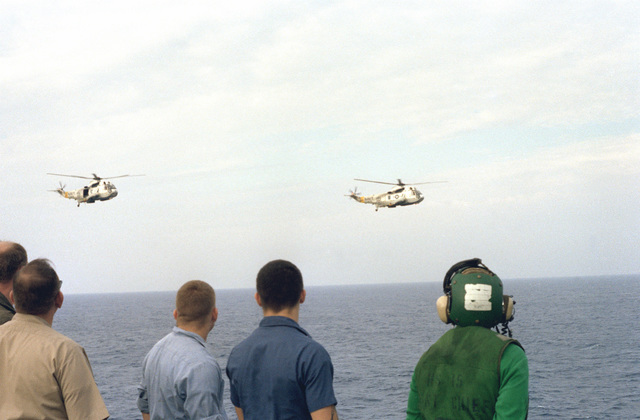 The helicopters assigned to the USS INDEPENDENCE (CV-62) fly by as crewmen watch from the aircraft carrier's flight deck
