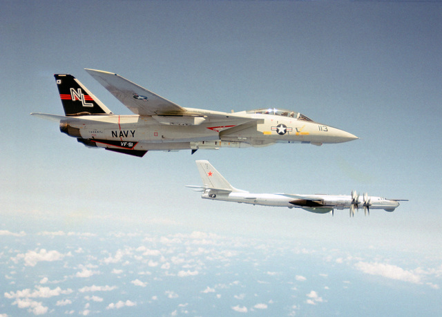 An air-to-air right side view of a Soviet F-14 Tomcat aircraft from Fighter Squadron 51 (VF-51) as it intercepts a Soviet Tu-95 Bear-A/B aircraft