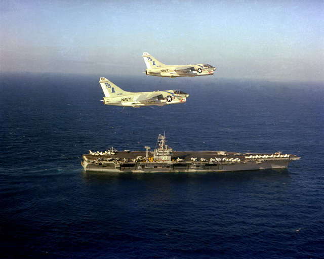 An aerial starboard view of the nuclear-powered aircraft carrier USS NIMITZ (CVN-68) underway with two A-7E Corsair II aircraft from Light Attack Squadron 82 (VA-82) in flight above the ship