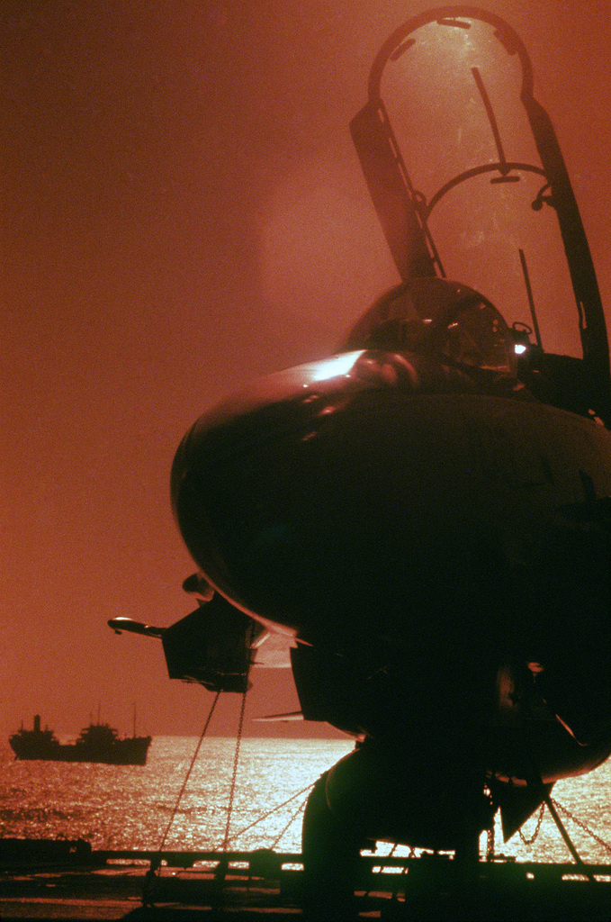 An aircraft is silhouetted by the setting sun on the flight deck of the aircraft carrier USS CONSTELLATION (CV 64)
