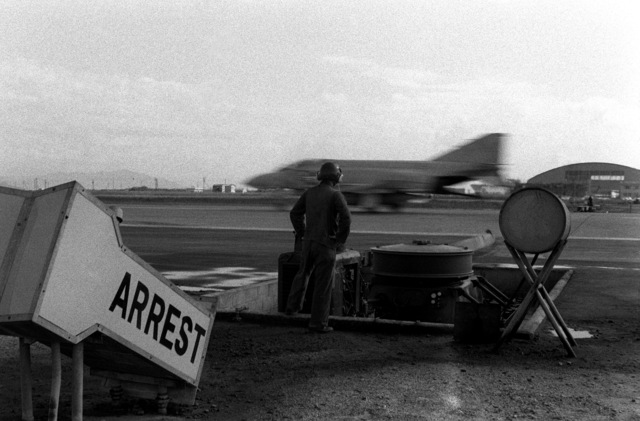 CPL Dave Fields, an aircraft arrestment systems operator, watches as an F-4 Phantom aircraft lands and its hook catches the arresting tape