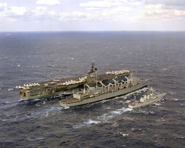 A starboard quarter view of the aircraft carrier USS INDEPENDENCE (CV-62), left, the fast combat support ship USS DETROIT (AOE-4), center, and the British frigate HMS SCYLLA (F-71) as the carrier is refueled by the support ship during a NATO exercise