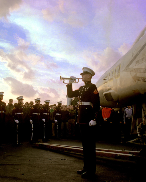 A U.S. Marine plays taps during a memorial service on the flight deck of the aircraft carrier USS INDEPENDENCE (CV-62). The service is being held for two pilots from Fighter Squadron 33 (VF-33)