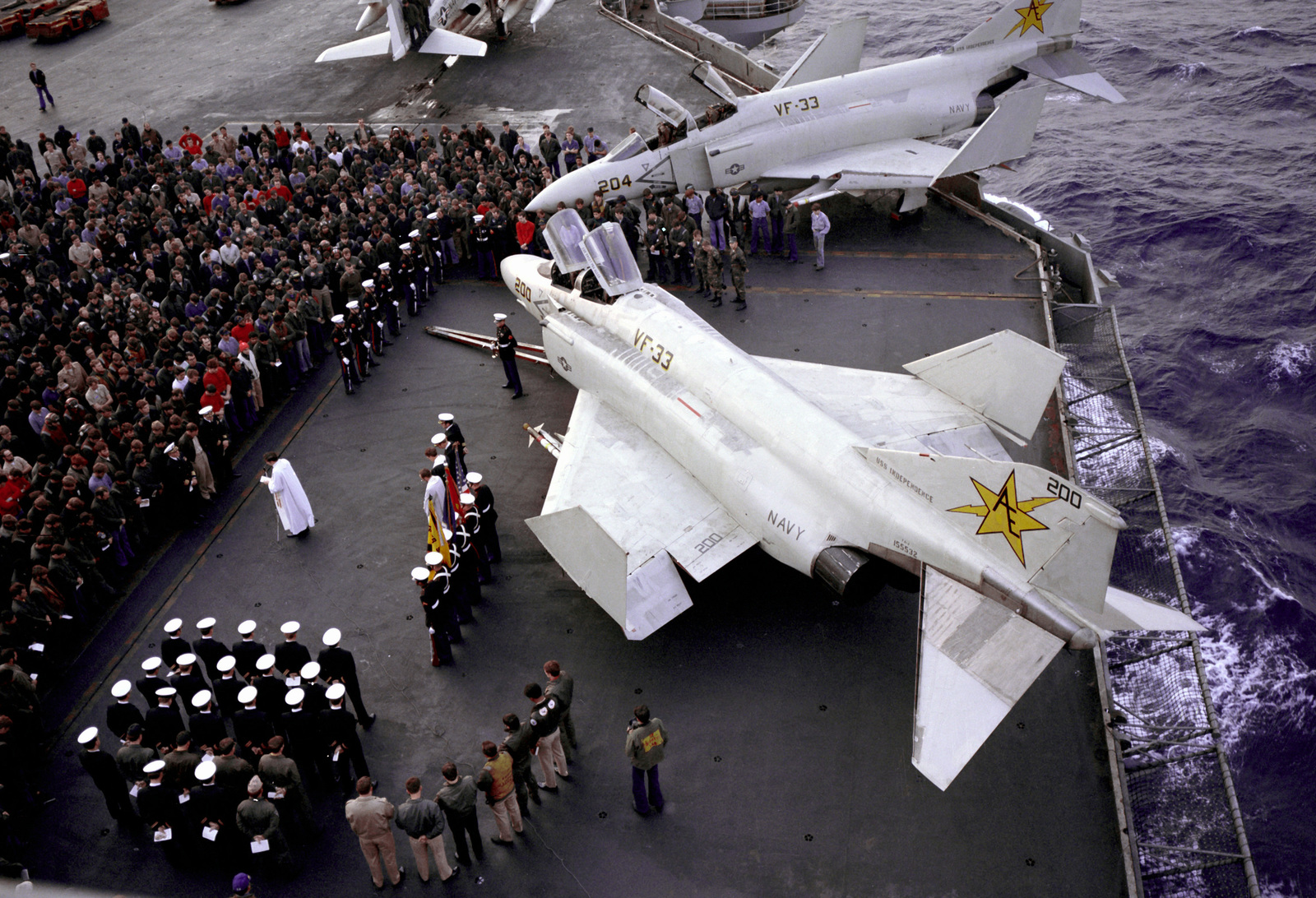 An overhead view of a memorial service underway on the flight deck of the aircraft carrier USS INDEPENDENCE (CV-62). The service is being held for two pilots from Fighter Squadron 33 (VF-33)