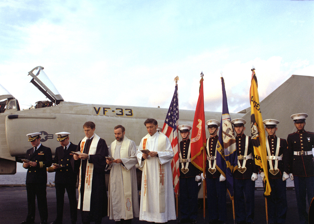 Officers, clergymen and a U.S. Marine Corps color guard stand near a fighter aircraft during a memorial service on the flight deck of the aircraft carrier USS INDEPENDENCE (CV-62). The service is being held for two pilots from Fighter Squadron 33 (VF-33)