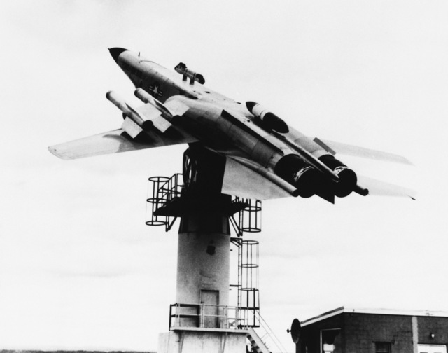 A full scale model of an Air Force F-111 fighter aircraft is mounted upside down on a test tower. This procedure is used to test the data link weapons control system