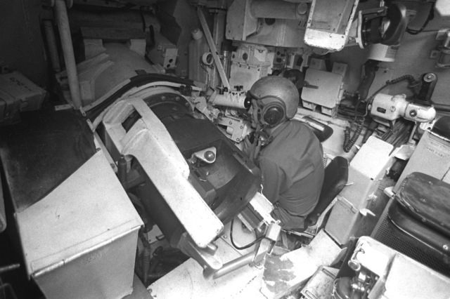 A gunner, inside the XM-1 Abrams tank, checks the fire control system