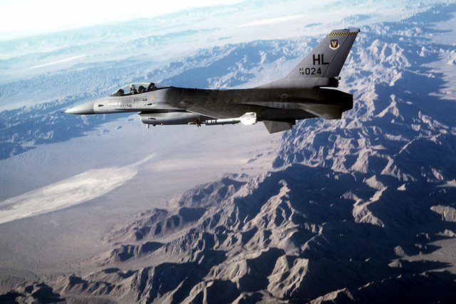 Air-to-air left side view of an F-16 Fighting Falcon aircraft armed with an AIM-9 Sidewinder air-to-air (AAM) missile