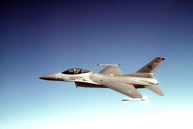 AN air-to-air left side view of an F-16 Fighting Falcon aircraft armed with an AIM-9 Sidewinder air-to-air missile on its left wing and an Air Combat Maneuvering Instrument pod on its right wing