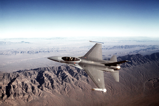 AN air-to-air view of an F-16 Fighting Falcon aircraft armed with an AIM-9 Sidewinder air-to-air (AAM) missile on its left wing and an Air Combat Maneuvering Instrumentation pod (ACMI) on the right wing