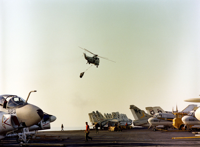 An SH-3 Sea King helicopter transports supplies from the oiler USS PASSUMPSIC (T-AO 107) to the deck of the aircraft carrier USS MIDWAY (CV 41) during vertical replenishment operations