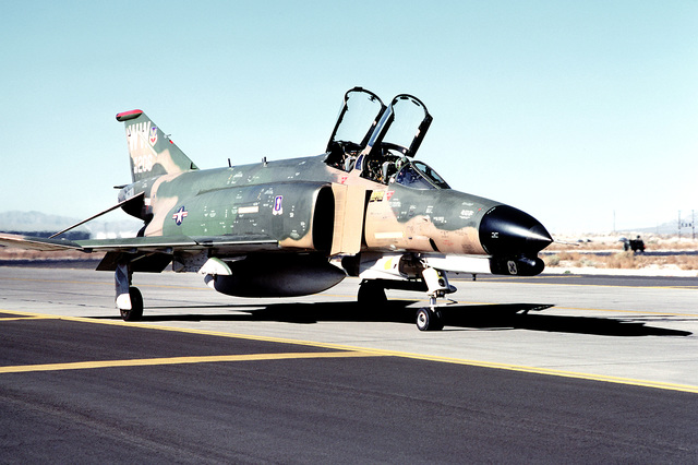 Front view of an F-4E Phantom II aircraft assigned to the 474th Tactical Training Wing, parked on the apron